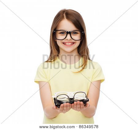 people and vision concept - smiling cute little girl in black eyeglasses holding many glasses in her hands