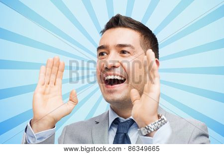 business, people and public announcement concept - happy businessman in suit shouting over blue burst rays background