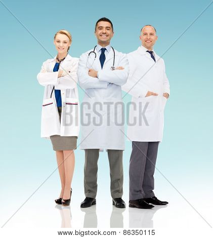 healthcare, advertisement, people and medicine concept - group of smiling doctors in white coats over blue background
