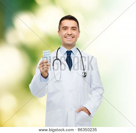 healthcare, profession, people and medicine concept - smiling male doctor in white coat with tablets over green background