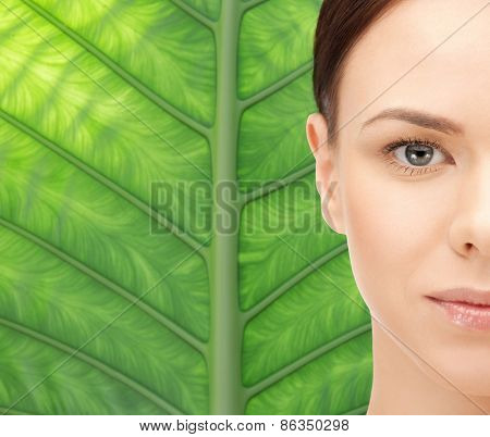 beauty, people, ecology, organic and health concept - beautiful young woman face over green palm tree leaf background