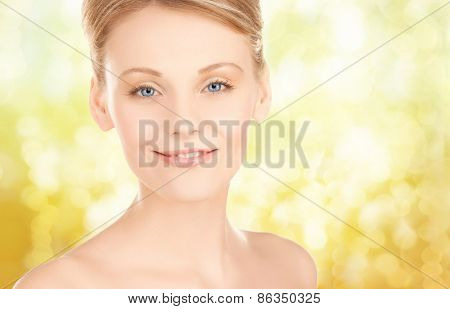 beauty, people and health concept - beautiful young woman face over yellow lights background