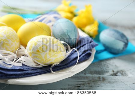 Easter composition with colorful eggs on napkin on wooden table background