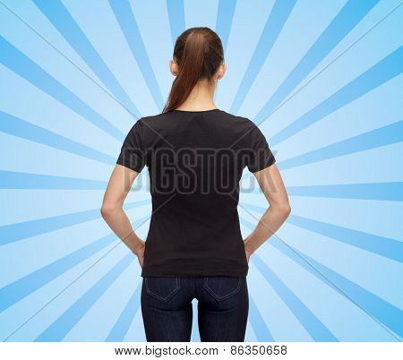 t-shirt design, advertisement and people concept - woman in blank black t-shirt over blue burst rays background from back