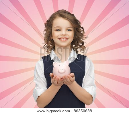 people, money, finances and savings concept - happy girl holding piggy bank on palms over pink burst rays background
