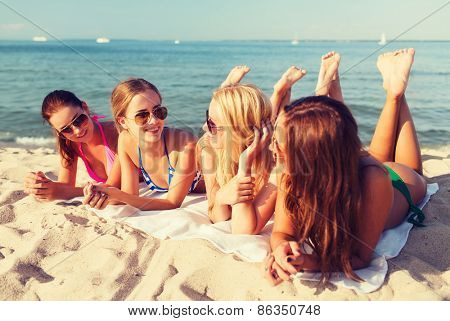 summer vacation, holidays, travel and people concept - group of smiling young women in sunglasses lying on beach