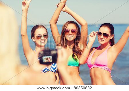 summer vacation, holidays, gesture and people concept - group of smiling women photographing by camera and showing peace sigh on beach