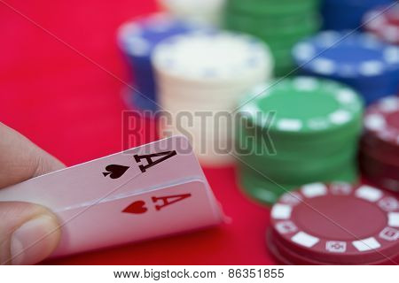 Poker Player Holding Two Aces Beside Lots Of Chips