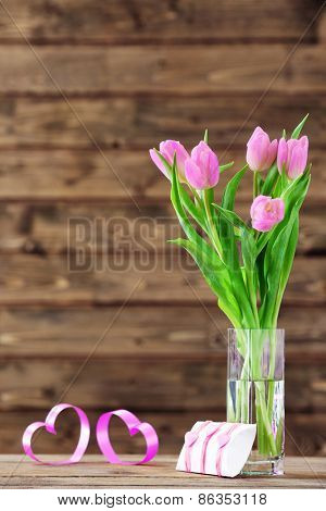 Beautiful pink tulips with present box on wooden background