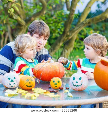 Young Dad And Two Little Sons Making Jack-o-lantern For Halloween In Autumn Garden