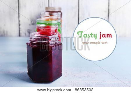 Homemade jars of fruits jam on table and color wooden planks background