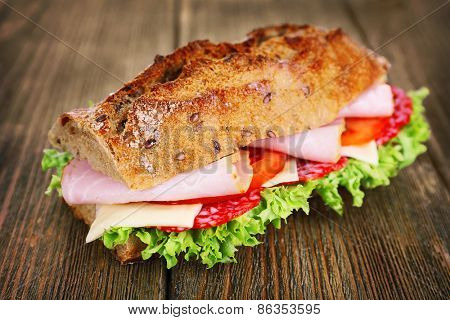 Fresh and tasty sandwich with ham and vegetables on wooden background
