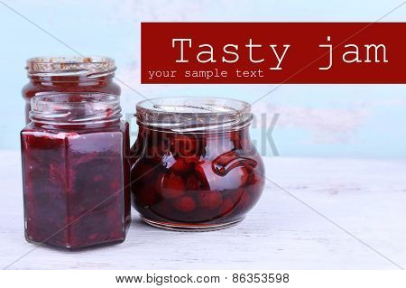 Homemade jars of fruits jam on wooden table and color wall background
