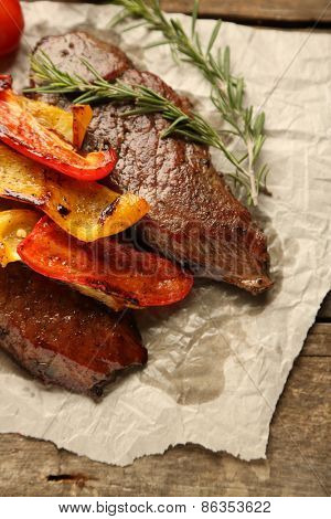Composition with tasty roasted meat on paper sheet, tomatoes and rosemary sprigs on wooden background