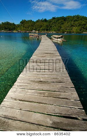 Wooden Jetty Over Tropical Beach