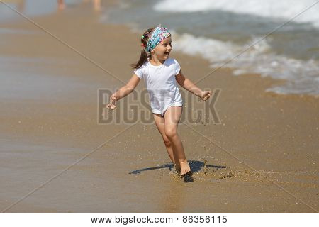 Child runs along the beach