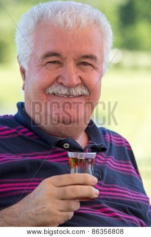 Smiling Senior Man Enjoying A Glass Of Tea