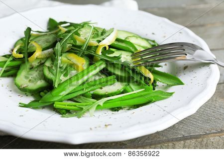 Green salad with cucumber, arugula and lemon peel on wooden table, closeup