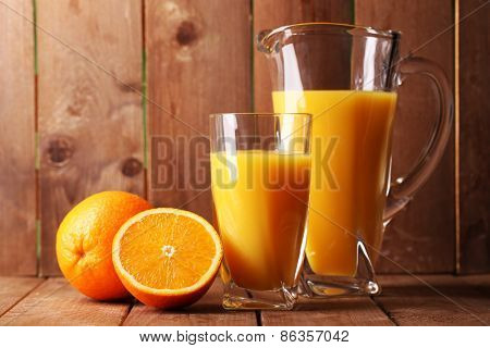 Glass and pitcher of orange juice on wooden table on wooden background