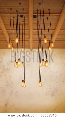 Ceiling Light Bulb Hanging On Pine Wood Against Warm Tone Of Grungy Cement Wall Use As Home Decorate