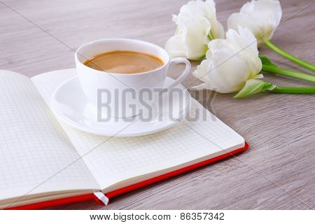 Beautiful tulips with diary and cup of coffee on wooden background