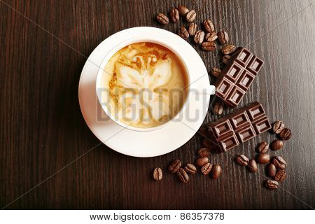 Cup of latte art coffee with grains and bar of chocolate on wooden background