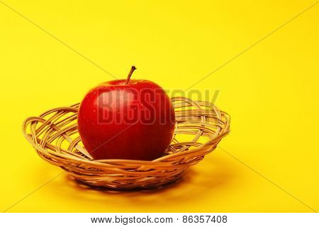 Apple in wicker basket on color background