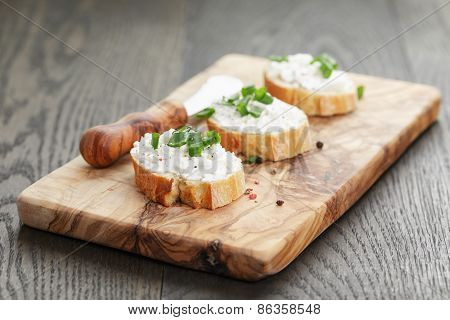 crunchy baguette slices with cream cheese and green onion on olive board