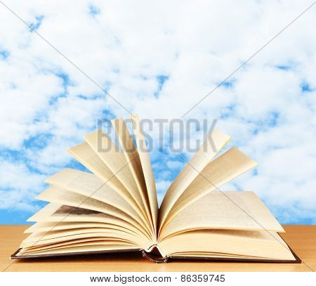 Opened book on table on sky background