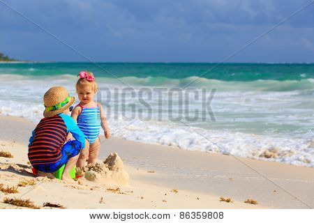 kids playing with sand on tropical beach