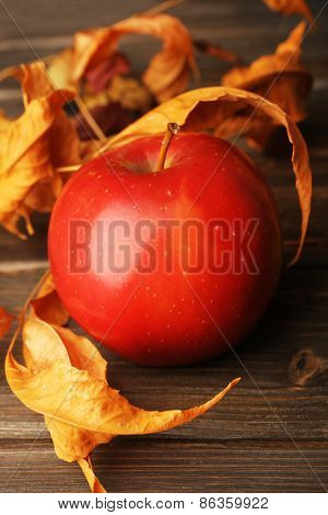 Apple with dried leaves on wooden table, closeup