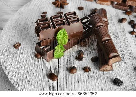 Stuffed chocolate with coffee beans and mint on wooden background