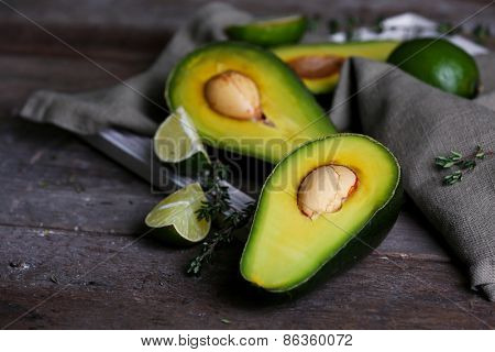 Sliced avocado with lime and herb on wooden table with napkin, closeup