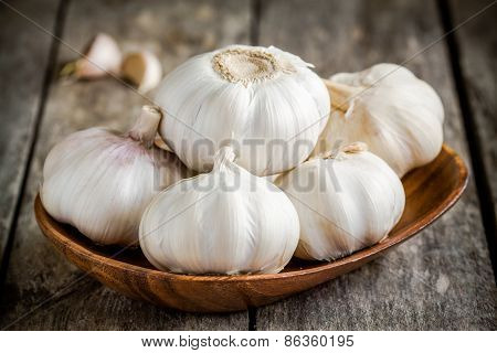 Organic Garlics In The Bowl On A Wooden Table