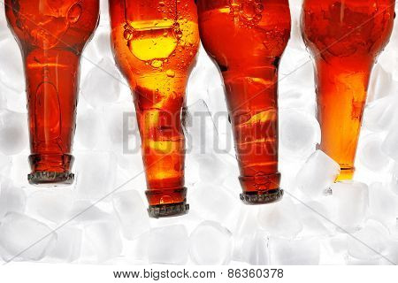 Glass bottles of beer with ice cubes, closeup