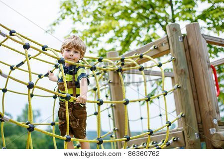 Cute Kid Boy Having Fun With Climbing On Children Playground