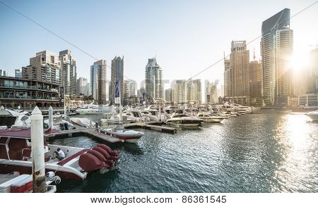 Dubai, United Arab Emirates - December 14, 2013: Panoramic view with modern skyscrapers and water pier of Dubai Marina at sunset, United Arab Emirates