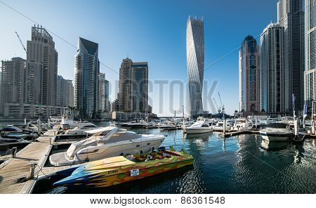 Dubai, United Arab Emirates - December 14, 2013:  Panoramic view with modern skyscrapers and water pier of Dubai Marina, United Arab Emirates