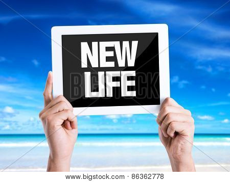 Tablet pc with text New Life with beach background