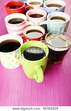 Many cups of coffee on pink background