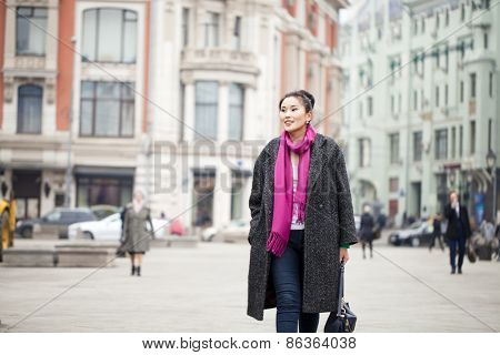 Young beautiful asian woman in stylish gray coat on a background of spring street