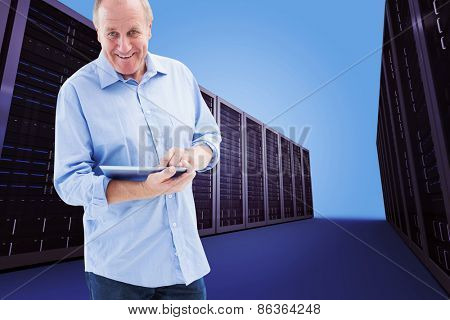 Happy mature man using his tablet pc against server hallway