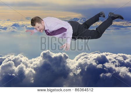Businessman falling down over clouds in background
