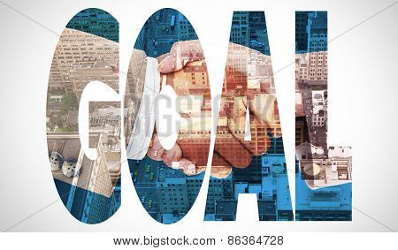The word goal and side view of business peoples hands shaking against new york