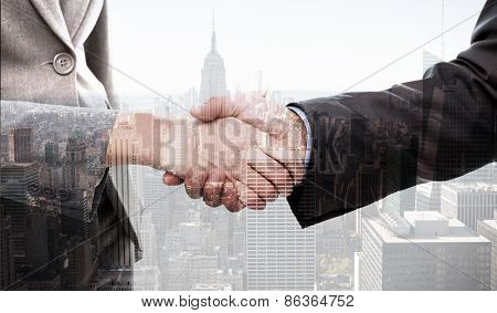 Close up of two businesspeople shaking their hands against city skyline