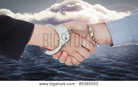 Business people in handcuffs shaking hands against calm sea with lighthouse