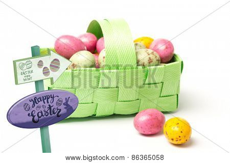Easter egg hunt sign against colourful little easter eggs in a green wicker basket
