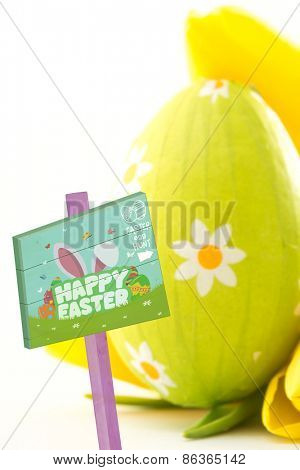 Easter egg hunt sign against green easter egg with yellow tulips
