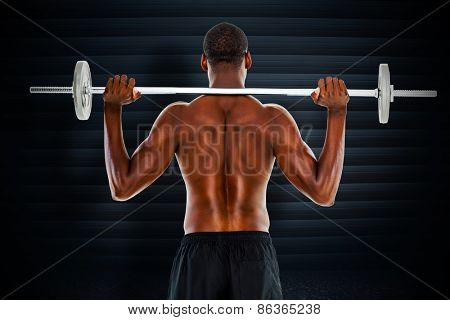 Rear view of a fit shirtless man lifting barbell against black background