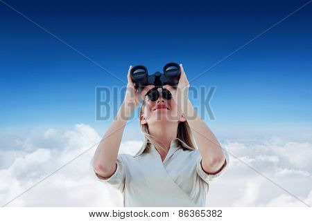 Businesswoman looking through binoculars against blue sky over clouds